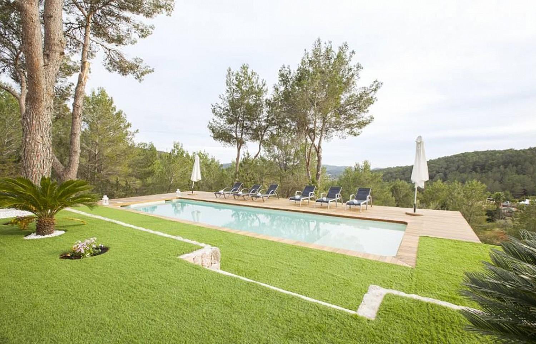 Jardín con piscina y hamacas