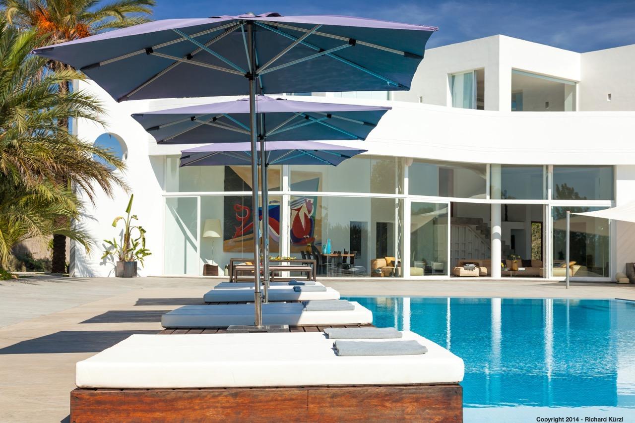 Tumbonas con sombrillas junto a la piscina exterior