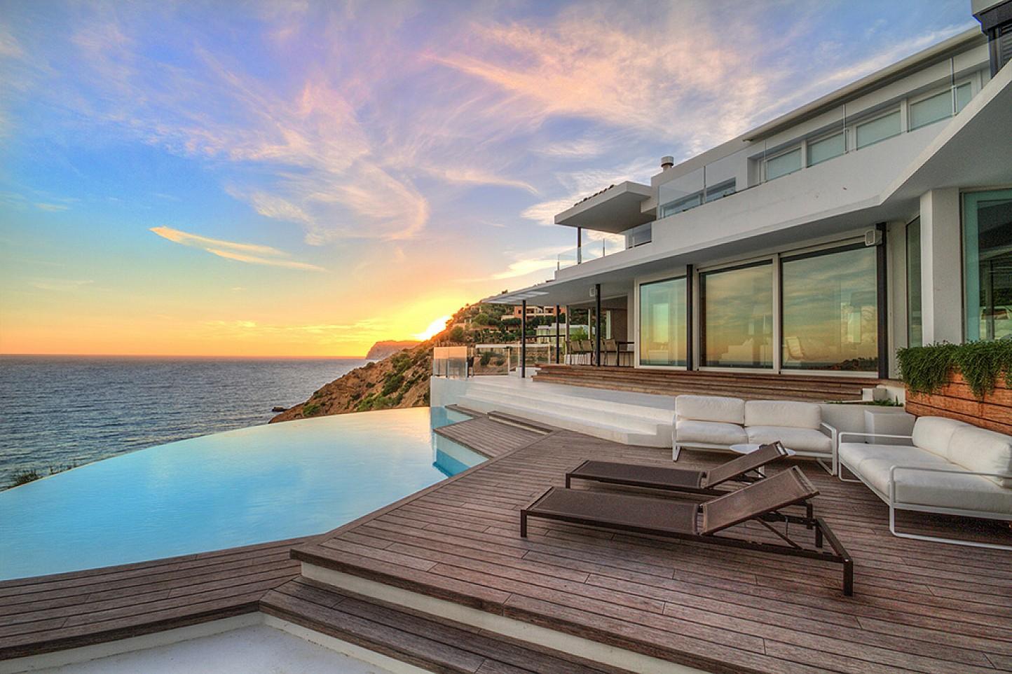 Vistes exteriors de la casa amb la gran piscina i les vistes al mar