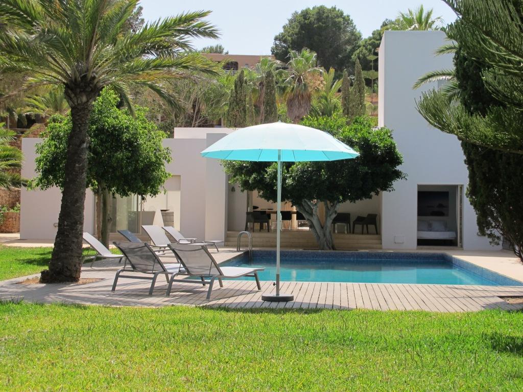 Gran piscina en el jardín con hamacas