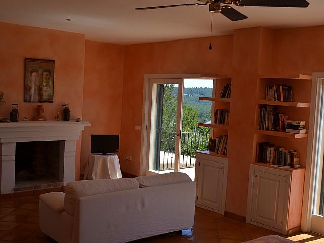 Salón amplio con chimenea y salida a la terraza