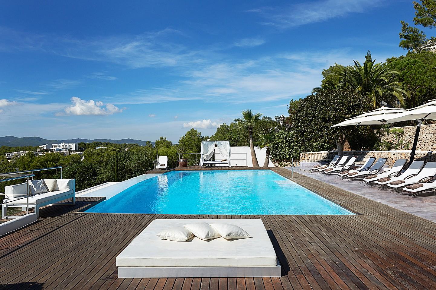 Esplèndida piscina rodejada d'hamaques