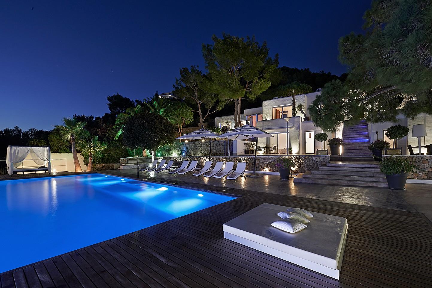 Buena iluminación nocturna de la piscina y la casa