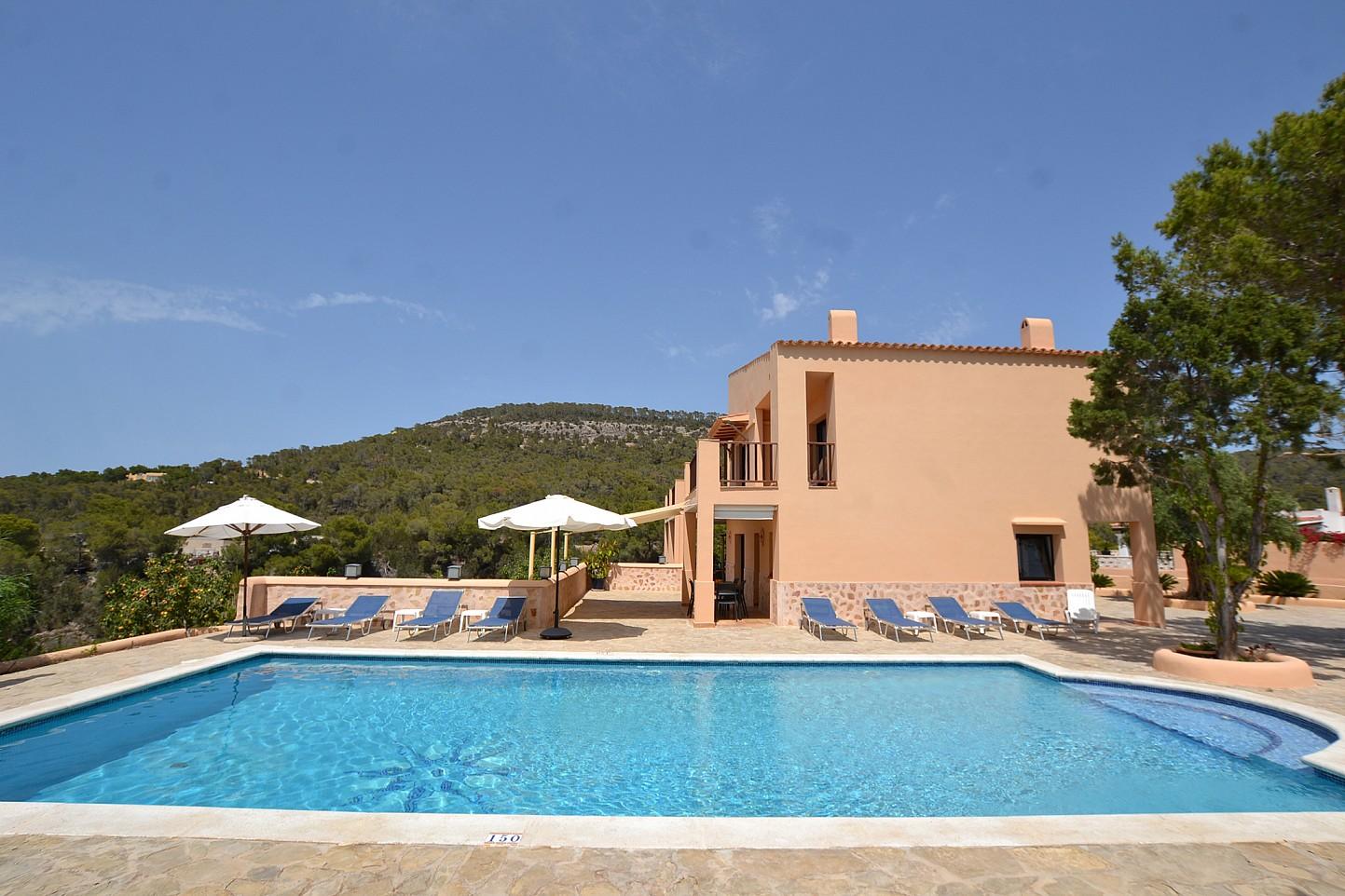 Gran piscina con hamacas en la parte lateral de la villa