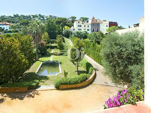 Vista de la piscina en jardín de lujoso palacete en venta en la Costa Brava