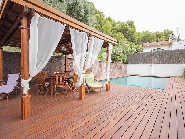 Terrasse en bois au bord de la piscine dans une maison de luxe en vente à Sitges